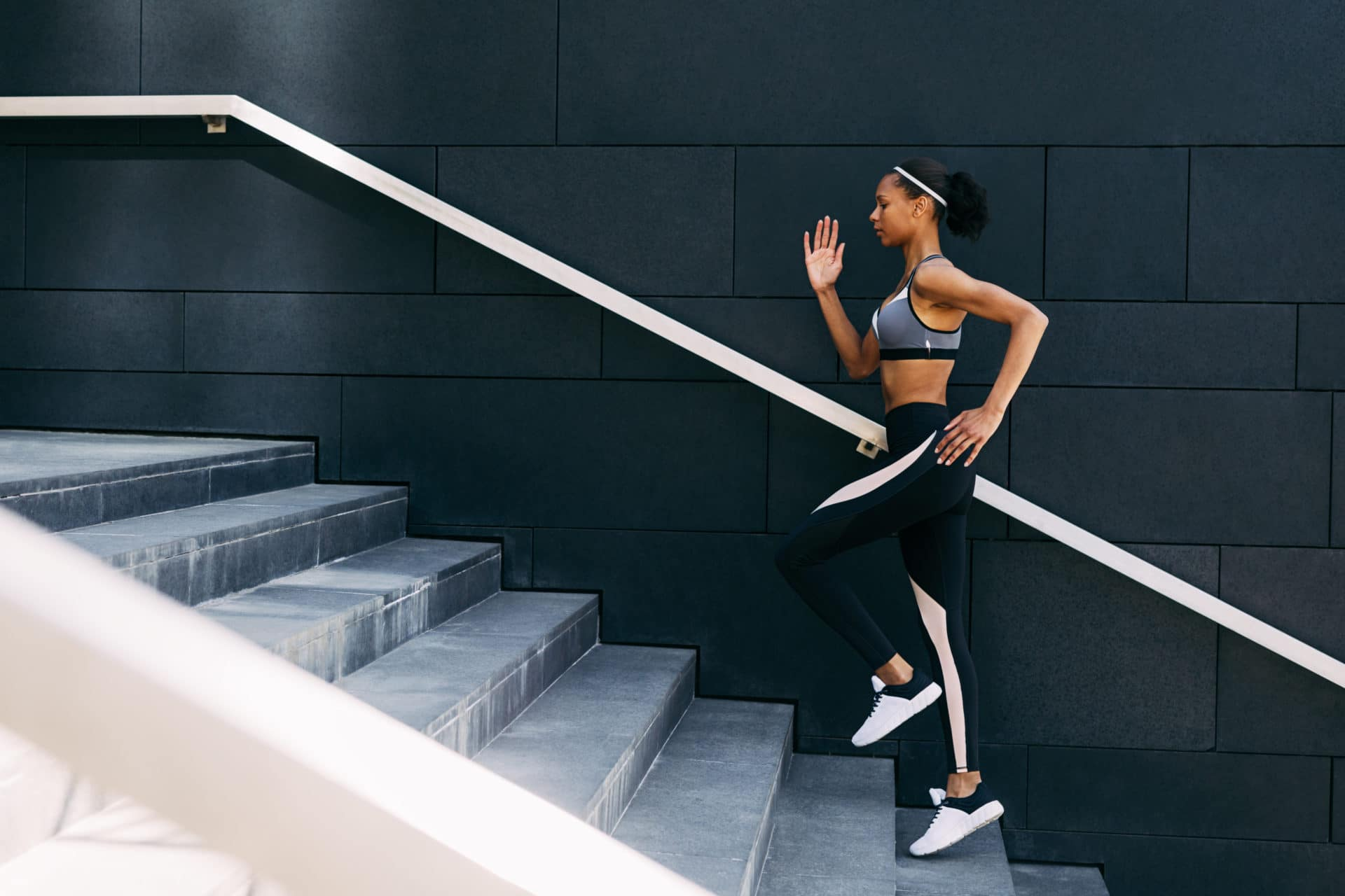 Side view of woman in sportswear  running up the steps in the city. Female athlete doing workout at the day.